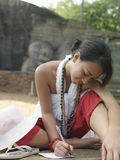 Woman Writing Paper With Sleeping Buddha Statue Behind. Young mixed race woman writing paper on ground with statue of sleeping Buddha in background Stock Photo