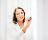 Woman writing with pen in the air. Business, office, technology and education concept - smiling woman writing with pen in the air Stock Photography
