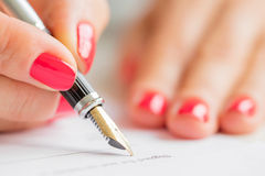 Woman writing with pen Royalty Free Stock Photo