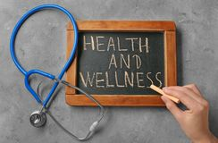 Woman writing phrase Health and wellness on blackboard stock images