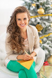 Woman writing in postcard near christmas tree Stock Photos
