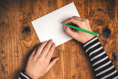 Woman writing recipient address on mailing envelope Royalty Free Stock Image