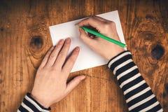 Woman writing sender address on mailing envelope Royalty Free Stock Photography