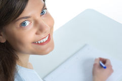 Woman, writing, smiling. Close-up of a smiling young woman, writing on a paper royalty free stock photo