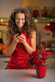 Woman writing sms in christmas decorated kitchen Stock Images