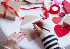 Woman writing something on envelope Royalty Free Stock Image