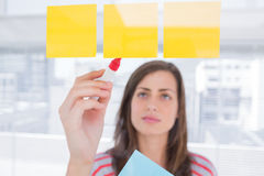 Woman writing on sticky note Royalty Free Stock Images
