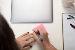 Woman writing a sticky note reminder royalty free stock image