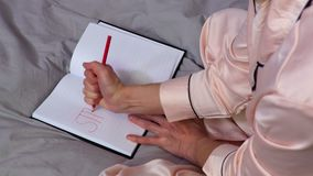 Woman writing stress word in red on notebook stock footage