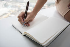 Woman is writing to notebook Royalty Free Stock Image