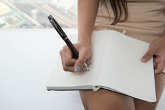 Woman is writing to notebook Stock Images