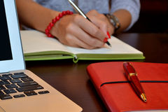 Woman writing to the notebook network concept. On the table laptop, two notebooks and pen. lady make notese notebook during the meeting with someone stock photos