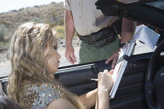 Woman Writing On Traffic Ticket. Beautiful young women writing on traffic ticket with traffic cop standing by her car Stock Image