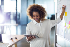 Woman writing on whiteboard while holding digital tablet Royalty Free Stock Images
