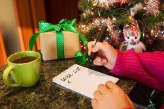 Woman writing wish list, with presents and christmas tree on background. Happy new year concept Royalty Free Stock Photography