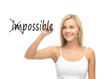 Woman writing the word (im)possible in the air Stock Photography