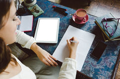Woman writing and working at home. Working at home concept. Entrepeneur business woman writing and taking notes using her digital tablet on retro desk full og Royalty Free Stock Photos