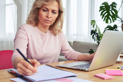 Woman writing while working in laptop Stock Photos