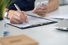 Woman writting something and looking at mobile phone Stock Photography