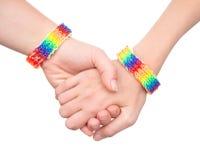 Woman& x27; 有作为彩虹旗子被仿造的镯子的s手 在白色 免版税库存照片