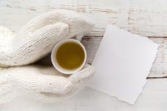 Woman& x27 ; mains de s dans les gants tenant une tasse de thé avec la carte vierge sur la table en bois blanche Images libres de droits