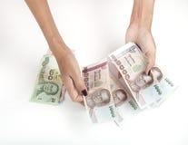 Woman' manos de s con los billetes de banco del baht de Tailandia Fotos de archivo