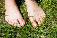 Woman& x27; piedi nudi di s in erba verde Immagini Stock