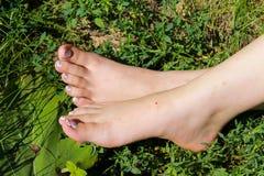 Woman& x27; piedi nudi di s in erba verde Immagini Stock Libere da Diritti