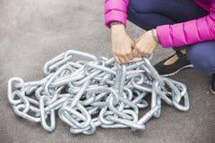 Woman& x27; s arma intentar aumentar una cadena metálica pesada Foto de archivo libre de regalías