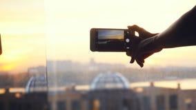 Woman& x27; s-Hand, die zu Hause Fotos der Stadt auf nahem hohem des beweglichen intelligenten Fensters des Telefons macht Stockbilder