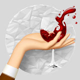 Woman's hand holding a wineglass with splashed wine on crumpled paper circle. Stock Image