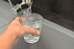 A woman& x27;s hand pours water into a glass Stock Photography