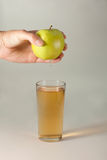 A woman& x27;s hand squeezes fresh juice. Pure apple juice pouring out from fruit into glass. Stock Photography