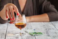 A woman's hand is touching a glass of cognac Stock Images