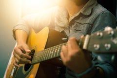 Woman& x27; s handen die akoestische gitaar spelen Stock Foto's