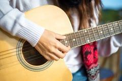 Woman& x27; s handen die akoestische gitaar spelen Royalty-vrije Stock Foto's