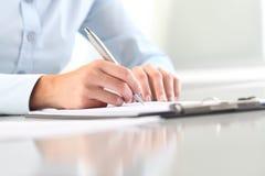 Woman& x27; s handen die op klembord met een pen schrijven Royalty-vrije Stock Foto