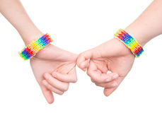 Woman's hands with a bracelet patterned as the rainbow flag holding on to little fingers.  on white Stock Photos