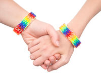 Woman's hands with a bracelet patterned as the rainbow flag.  on white. Royalty Free Stock Photos