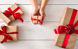 Woman's hands give christmas gift in present box Royalty Free Stock Photography