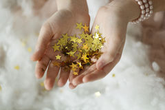 Woman's hands holding golden tinsel stars Stock Images