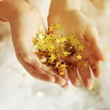 Woman's hands holding golden tinsel stars Royalty Free Stock Images