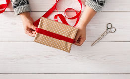 Woman's hands wrapping christmas holiday present with red ribbon Stock Image