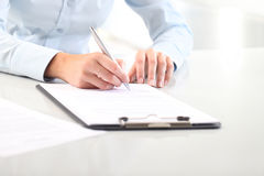 Woman's hands writing on sheet of paper in a clipboard and a pen Stock Image