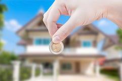 Woman& x27; s overhandigt holdingsmuntstuk op huisachtergrond, de investering van de het huiseigendom van besparingsonroerende go Stock Foto's