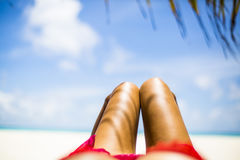 Woman's tanned legs on white sandy beach, Maldives Stock Photos