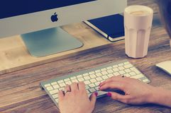 Woman's hands on Apple keyboard Stock Photos