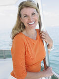 Woman On Yacht Smiling. Portrait of middle aged woman on yacht smiling Royalty Free Stock Image