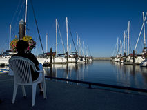 Woman and yachts. Woman resting in garden chair at marina enjoying view of docked yachts Stock Photo