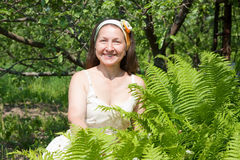 Woman in yard  with fern Stock Images
